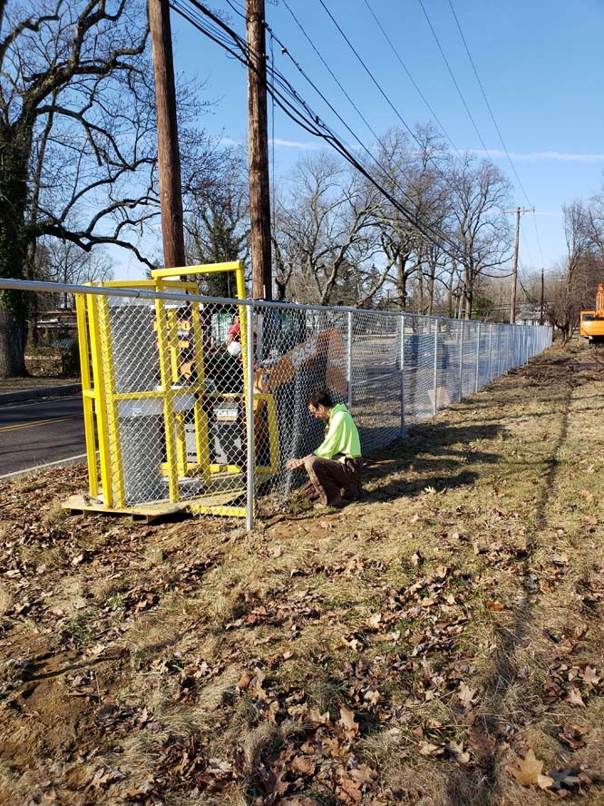 Crew installing chain link fence